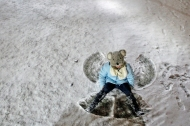 Christopher Newport University student Amy Saunders sits up after making a snow angel on the campus Monday evening. (Jonathon Gruenke/Daily Press)