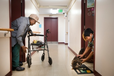 "James Lee Britt, 77, bends down to say hello to Janine Vandenberg's cat, One Sock, and chats with Vandenberg before he heads back into his apartment at Melrose Towers on Wednesday, June 17, 2015. Britt had just returned from picking up some food items downstairs at the weekly food delivery through the Joint Residents Council of the Roanoke Redevelopment and Housing Authority and the Melrose Towers Council. Fitted with dentures last month after not wearing any for 15 years, Britt says he is more social now and talks more with his neighbors and friends. ""I thought they would forget the poor people, but they're not. That's why I'm kind of speechless. I'm getting everything that I didn't get before. And I'm happy about it,"" Britt said."