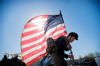 Mike Lafferty of the 7th Maryland places returns to camp with the American flag on Saturday after the Appomattox Historical Society's reenactment of the Battle of Appomattox Court House.