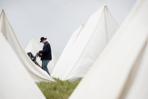 "Re-enactor Brady Vail from the 20th Indiana sets up a tarp over his tent in preparation of the expected rain on Friday at the Appomattox Historical Society's ""Long Road Home"" program at the Appomattox Center for Business and Commerce on Friday."