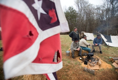 Members of the 11th Virginian Company G and 5th Virginian Infantry talk by the fire at their camp at Appomattox Court House National Historic Park.