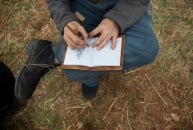 Russell Chu with the 11th Virginia Company G draws a photo of Gen. Robert E. Lee in his notebook at the Confederate camp.