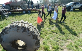 Baylee Hart makes her way through the mud hop pits after getting dressed for her senior prom with an entourage of younger girls in tow.