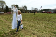 Baylee Hart transfers her white prom dress to a nearby camper where she will prep for her senior prom after competing in the Muddin' at the Moose mud hop on Saturday, April 11, 2015.