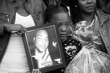 "--General News 3rd Place: Scott Elmquist/Style Weekly--During a vigil, Keyari Edwards, 7, holds a photograph of her father Kiarri ""Kee Kee"" Edwards, who was murdered in a shooting on Dinwiddie Avenue."