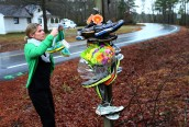 """Gina Junkermann places running shoes with the message of """"MEG STRONG WE LOVE YOU!"""" at the corner of Hickory Hill Road and East Patrick Henry Road in honor of Meg Menzies, who died a day before after being struck by a car driven by a drunken driver."""