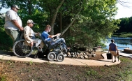 --Lifestyle HM: Alexandra Welch Edlund/Richmond Times-Dispatch--James Howard helps slow down Vance Sutphin's wheelchair as Anthony Pendergrast guides it as they descend to the fishing dock during a retreat at Howard's home for veterans from McGuire VA Hospital's Spinal Chord Injury Unit Thursday, June 5, 2014. Nancy Wellons, James' mother, carries the fishing pole. Pendergrast is a bus drive at the hospital.