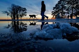 --Pictorial 2nd Place: Jonathon Gruenke/Daily Press--Patrik and Camilla Lasson walk their dog Roxy as snow piles melt while the sun sets Friday evening near Lions Bridge.