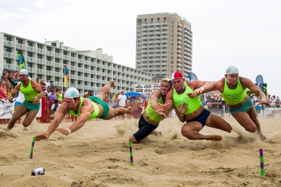 --Sports Action 1st Place: Peter Casey/Freelance--Virginia Beach, VA, USA; Competitors dive at the finish of the second round of the beach flag race finals during the 2014 USLA National Lifeguard National Championships.