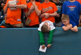 --Sports Feature HM: Bill Tiernan/The Virginian-Pilot--Cullen Kirk,9, of Virginia Beach( green sleeves) rests over the wall along third base during a break in light rain showers as he waits for Orioles players to sign autographs at Harbor Park Saturday afternoon, March 29, 2014 before the Orioles exhibition game with the Norfolk Tides. Cullen is a Red Sox fan according to his dad.