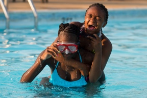 Sahara McKnight, 12, holds onto Promise Guy, 13, as they rise from underwater while swimming in the pool at the Presbyterian Home in Lynchburg, Va. Swimming was one of Sahara's favorite activities during her stay with the Austin family.