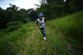 Promise Guy, 13, and Sahara McKnight, 12, run up the hill, screaming, as they try to escape the rain, which brought an end to their evening fishing trip at a pond in Bedford, Va. The girls are part of The Fresh Air Fund of New York City, which sends thousands of children every year to rural homes so they can experience life outside the city.
