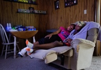 Sahara (left) and Promise (right) cuddle together on the recliner as they watch TV on a slow day at their host family's home in Madison Heights, Va.
