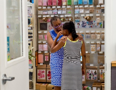 Barbara Austin comforts Sahara as she wipes away tears after frustrations from making rubber band jewelry led her to take a break from the class at Michaels in Lynchburg, Va.