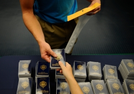 Ensign Ryder Ashcraft distributes copies of Reef Points to incoming plebes at the US Naval Academy in Annapolis, Md., on Tuesday, July 1, 2014.