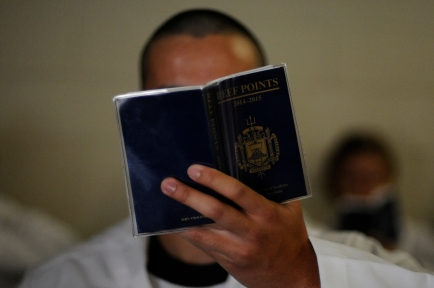 A plebe studies his copy of Reef Points on Induction Day at the US Naval Academy in Annapolis, Md., on Tuesday, July 1, 2014.