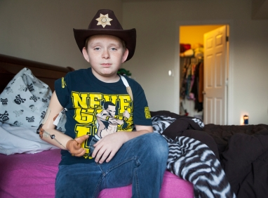 --Feature Picture Story 3rd Place: Griffin Moores/The News-Leader--Matthew Mitchell sits for a picture in his room wearing his prosthetic arm. Although the arm is intended to aid in completing everyday tasks his mom Lori Mitchell describes it more as a hinderance for the 11-year-old. While Matthew was developing in the womb, a thin strand of tissue wrapped so tightly around his arm that the limb failed to fully form, a condition called amniotic band syndrome that may contribute to two percent of all miscarriages. Since he was a baby, he has had to find ways to adapt to life with only a left hand. That has done little to hold him back.