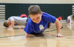"Matthew struggles through a round of pushups during gym class at Wilson Elementary School. Hunter Ingersoll, Matthew's P.E. teacher, says he admires the 10-year-old's spirit and unwillingness to use his disability as an out for difficult activities. ""IÕve never seen the kid when he wasnÕt smiling and it really made me feel good for him to come in and try whatever we were doing,"" Ingersoll said."