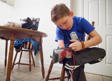 "Matthew ties his shoes while getting ready for school. Figuring out how to knot his laces with one hand wasn't easy, but as his 4th grade teacher Martina Carroll explains, his ""let me keep going"" attitude carried him through."
