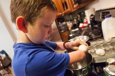 Matthew Mitchell cracks an egg while cooking breakfast early in the morning before heading to school.