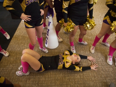 """--News Picture Story 1st Place: Griffin Moores/The News-Leader-- """"Cheer"""" Waynesboro High School's Sonny Carey stretches her arms on the ground in preparation for the team's cheerleading state championship performance in Richmond on Nov. 8, 2014. With emotions running high and the weight of an entire season riding on their shoulders, the annual cheerleading competition brings dozens of teams from around Virginia together to compete for the state championship."""