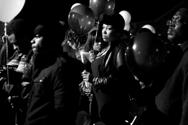 Former employees, friends and family hold candles and balloons during a vigil for Isaac Oshin outside Majik City Gentlemen's Club and Sports Bar Friday evening. Dozens of people gathered outside the club to remember Isaac Oshin who was shot to death inside the club at 5825 Jefferson Avenue Wednesday evening.
