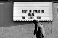 Terry Riddick walks past a sign during Friday evening's vigil for Isaac Oshin outside Majik City Gentlemen's Club and Sports Bar Friday evening. Dozens of people gathered outside the club to remember Isaac Oshin who was shot to death inside the club at 5825 Jefferson Avenue Wednesday evening.