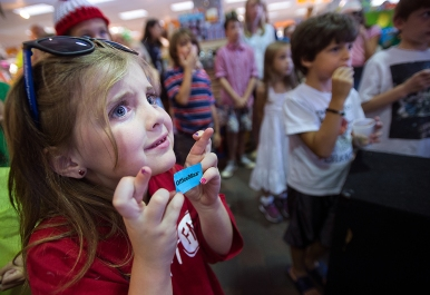 "Lilli Reynolds, 7, crosses her fingers as the winners of the raffle are announced during the ""Where is Waldo"" wrap-up party at Givens Books in Lynchburg, Va. Reynolds' mother, Heidi, won the adult grand prize, which consisted of gift cards and Waldo books. The month-long ""Where is Waldo"" event raised awareness of local businesses as children and adults searched for cutouts of Waldo hidden among stores."