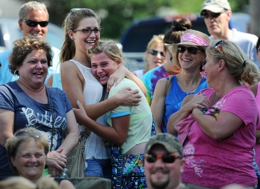 Emily Broeker, right, celebrates with her friend Emma Sykes after placing the winning bid on a Chincoteague Pony foal during the 90th annual Chincoteague Pony Auction on Thursday, July 30, 2015. Each year a portion of the Chincoteague Pony herd is auctioned off to benefit the Chincoteague Volunteer Fire Company, which owns and maintains the herd.