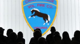 Spectators watch the 90th annual Chincoteague Pony Auction at the Chincoteague Carnival Grounds on Thursday, July 30, 2015. A portion of the wild herd is auctioned each year to benefit the Chincoteague Volunteer Fire Company, which owns and maintains the herd.