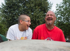 Timothy Nettles, 13, jokes around with his dad, John Nettles, as they pass time after dinner before being able to get back into their rooms at The Valley Mission in Staunton on Aug. 8, 2015.
