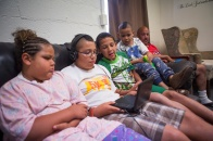 "John Nettles, right, looks on as his children watch a show together on a portable DVD player in the play room at The Valley Mission on Aug. 8, 2015. ""I wanted to try and make my kids feel at home,"" said Nettles, describing how he brought a TV into the shelter but had to take it out of their room due to one of the organization's policies. ""There's a lot of things that you can't have, but I still try anyway."""