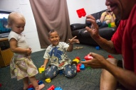 Christian Nettles, 5, tosses blocks at his dad, John Nettles, as they play together alongside 1-year-old Annabelle Thompson, another resident at The Valley Mission on Aug. 8, 2015.