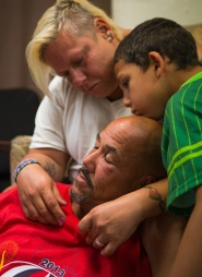 At the end of the day John and Constance Nettles relax with their son, Nicholas Nettles, 10, in the play room at The Valley Mission on Aug. 8, 2015.