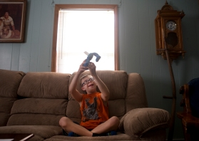 Devin Bailey, 9, plays with a toy Elmo doll while sitting on a couch at his father's home in Troutville Wednesday evening, Aug. 12, 2015. Devin cannot communicate basic information like his name, age or address and cannot count to ten, says his father Jimmy. Bailey has autism and Down Syndrome and attended Troutville Elementary School.