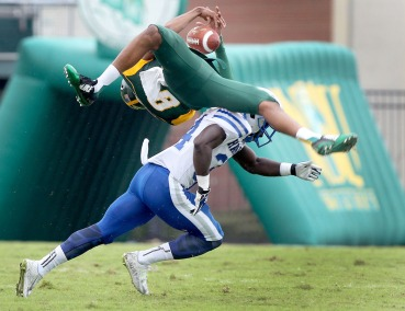 Norfolk's DeAndre Sangster manages to catch this first quarter pass as he is hit by Hampton's Chaka Diarrassouba during the first quarter Saturday September 26, 2015 in Norfolk.