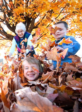 Virginia Mennonite Retirement Community resident Doris Bombarder, left, 84, helps Waterman Elementary School kindergartner Brody Williams, right, 5, cover classmate Gisele Butterfield, 5, in maple leaves while spending time outside the school Wednesday morning. VMRC residents have been in a Big Brothers Big Sisters program where they get paired with kindergartner as their GrandBigs.