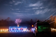 Demetri Masincup, 8, son of Shawnn Masincup, sits on the top of their car while visiting the Christmas light show at 6994 Tiltyard Drive in Dayton on Wednesday, December 16. The 35-minute long show had lights choreographed with music that played on the radio.