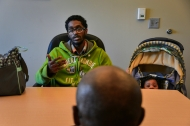 """With his daughter, Sapphire, curiously looking on, Paul Gayle explains to social worker Alphonso Pettis about being thrown out of his mother's house after a disagreement. At 19, he possessed what few other black men in his neighborhood did: He was among the 42 percent with no criminal record; the 35 percent with a high school diploma; and the 14 percent of fathers who lived with their child. """"A master at barely avoiding disaster,"""" his mother said of him, but she had said the same thing about Paul's father until he was shot and killed during an argument at 39, when Paul was in eighth grade."""