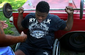 Edward Miller, (17 in 2014), exercises with the help of Rodney Debro, a neighbor, at Debro's backyard in Richmond on Tuesday, June 17, 2014. To prepare his spinal fusion surgery, Edward tried to lose his weight and build the muscle.