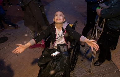 2nd PLACE LIFESTYLE: Todd Spencer, Virginian-Pilot---Eleven-year-old Michaeyla Nadeau, who has been diagnosed with osteosarcoma, reaches up from her wheelchair as simulated snow falls from the roof of the Children's Museum of Virginia during the Snow Wonders event outside the museum in Portsmouth, Virginia.