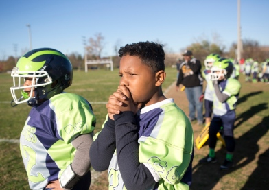 Jerel Rhodes, (22), left, and Carlos CJ Beattie-Cicero, (69), right, follow the play closely on the sidelines with his teammates during their AAU game against the Richmond Eagles at the Rivers Edge Sports Complex on Saturday, Nov. 14, 2015. The Wolverines, the first American Athletic Union team of its kind in Roanoke, won its game 24-19 and went undefeated in their season 8-0. They are headed to Lynchburg next week for the state championship at E.C. Glass High School.