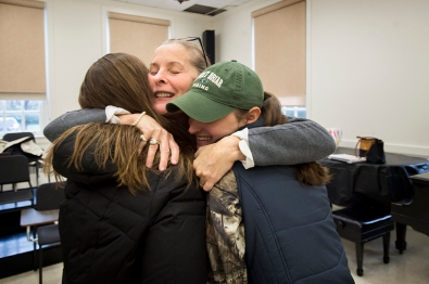 Marcia Thom-Kaley hugs students Hallsey Brandt (left) and Katie Fisher at the start of their music appreciation class, thanking them for a gift the students recently got their teacher. The professors close relationship to their students is one of the things that draws women to the school.