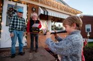 Reuben Miller, 5, of Harrisonburg, plays Christmas songs on a recorder for neighbors Pat Hedrick, at right, and Lewis Siever for donations as he helps raise money to cover the costs of a heart pump for his great-uncle, Kenneth Dove Jr.