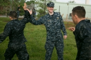 Lt. George Yacus, a staff member at the Center for Academic Excellence, greets plebes as they exit the Severn River during the annual Sea Trials exercise at the U.S. Naval Academy in Annapolis, Md., on Tuesday, May 12, 2015. The event, modeled after the Marine Corps' Crucible and Navy's Battle Stations events, runs over 14 hours and tests the plebes' physical and mental endurance.