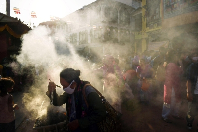 Smoke engulfs people as they celebrate Buddha Purnima which commemorates the birthday of Buddha near the Boudhanath stupa on Monday May 04, 2015 in Kathmandu, Nepal. The ceremony took on a deeper significance being a little over a week after a deadly earthquake killed thousands.