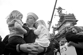 Petty Officer 1st Class Tim Walden holds his two-year-old daughter, Teagan, left, and three-year-old daughter, Zoe, right, after the USS George Washington arrived at Naval Station Norfolk Thursday morning December 17, 2015.