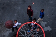 3rd PLACE SPORTS ACTION: Jahi Chikwendiu, Washington Post---Youngsters hoop on a portable basketball goal brought through their West Baltimore neighborhood by the city's parks and recreation division on November 17, 2015, in Baltimore, Maryland. The goals are regularly rotated around the city in an effort to divert kids from the negatives of the streets.
