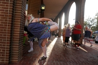 HM SPORTS FEATURE: Jonathon Gruenke, Daily Press---Chris Wharton stretches before participating in the Drag Race on Queens Way during Saturday's Hampton Block Party. Four teams representing different charities ran down Queens Way in heats.