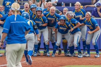 HM SPORTS FEATURE: Austin Bachand, Daily News Record---Hofstra junior Caryn Bailey gets welcomed to home base by the rest of her team after she hit a home run during their CAA Championship game against James Madison University on Thursday, May 7.